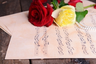 Beautiful roses with pearls on music sheets on wooden table, closeup